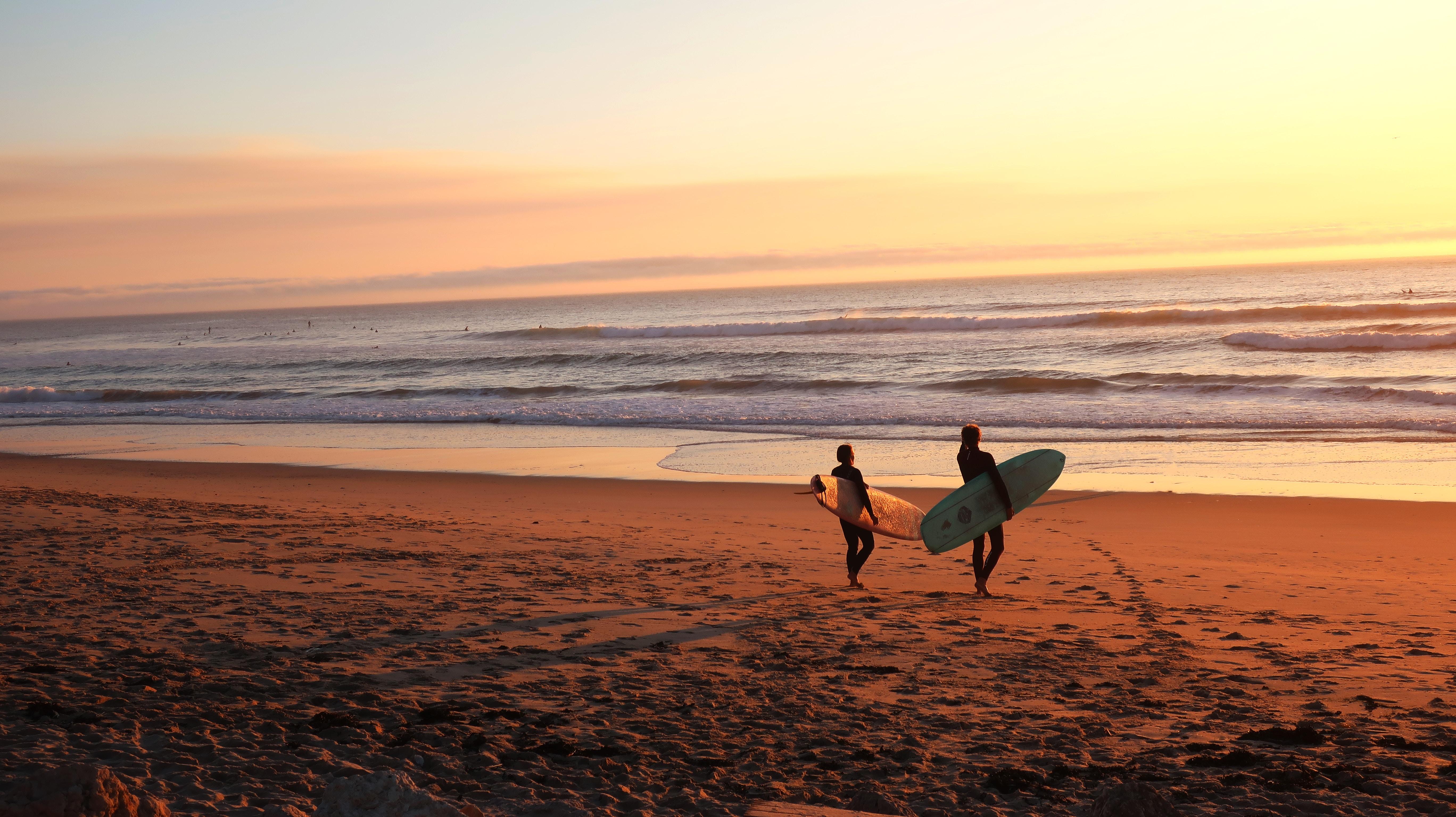 Surfer beobachten den Sonnenuntergang am Strand