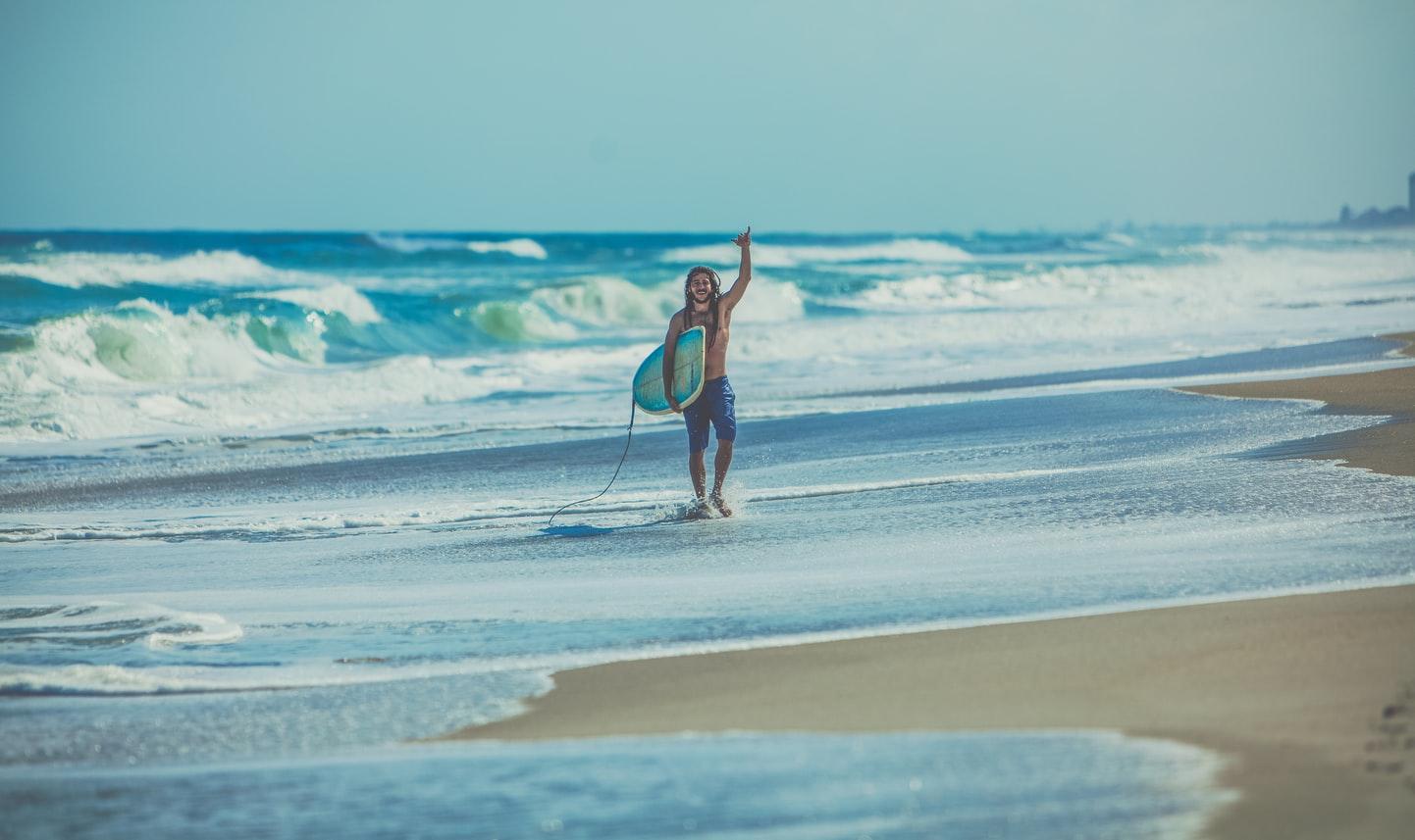 Happy Surfer mit Surfbrett